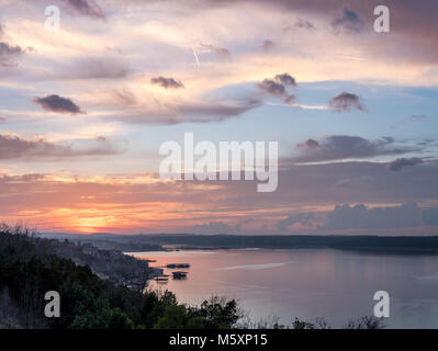 High Resolution Picture of Sun setting behind Hills with Lake in the Foreground - Stock Photo