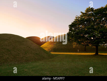 The sun rise over the Tumuli park royal tombs complex located in Gyeongju, South Korea. - Stock Photo