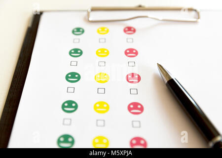 Customer service evaluation survey with smiley faces and pen. - Stock Photo