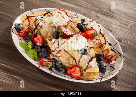 Pancakes with cream and fruit on wooden table - Stock Photo