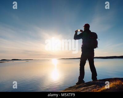 Tourist with phone in hand and backpack stand on a rock. Hiker looking over blue sea and taking photo by his smart - Stock Photo