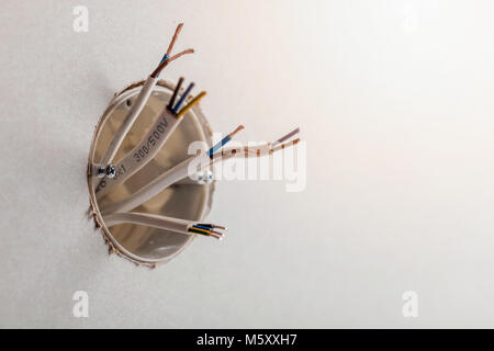 electrical cables out of wall socket - Stock Photo