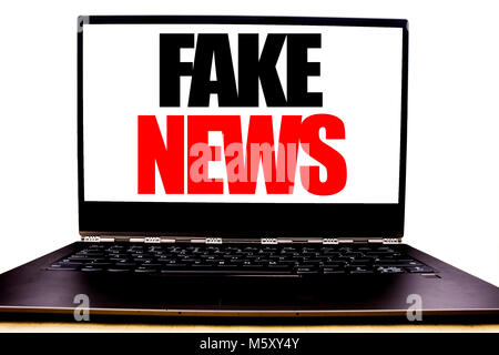 Handwritten text showing Fake News. Business concept writing for Hoax Journalism Written on monitor front screen, - Stock Photo