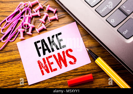 Handwritten text showing Fake News. Business concept for Hoax Journalism written on pink sticky note paper on wooden - Stock Photo