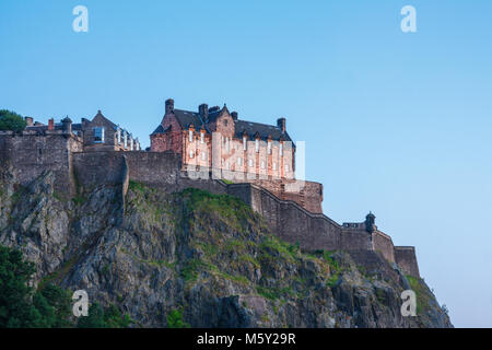 Steep cliffs with walls and the hospital building of Edinburgh castle seen from the north under a blue sky during - Stock Photo