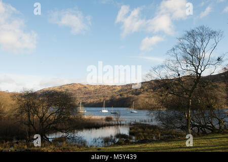 Coniston Water from Lake Bank with some moored sailing boats sitting in the bay. - Stock Photo