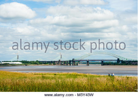 People walking along the footpath at Pickering's Pasture in Widnes with The New River Mersey Gateway Toll Bridge - Stock Photo