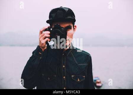 One man Travel around the world with one camera,Man holding camera on hand and standing at sea,man taking photo - Stock Photo