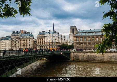 People o the bridge over Seine river and typical parisian buildings on background in Paris, France. - Stock Photo