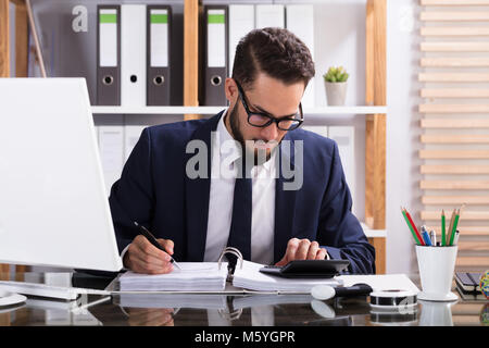 Businessman Calculating Bill With Calculator In Office - Stock Photo