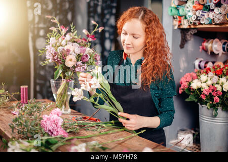Portrait of young female florist holding white flowers and looking at them. - Stock Photo