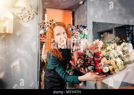 happy shop assistant showing prepared rich floral bouquet at store - Stock Photo