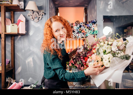 cheeful young florist standing next to bouquets of vernal flowers in shop - Stock Photo