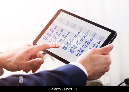 Close-up Of A Businessperson's Hand Using Calendar On Digital Tablet Stock Photo