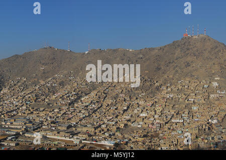 Aerial photo of an informal settlement on the hillside of Kabul in Afghanistan with transmission towers on top of - Stock Photo