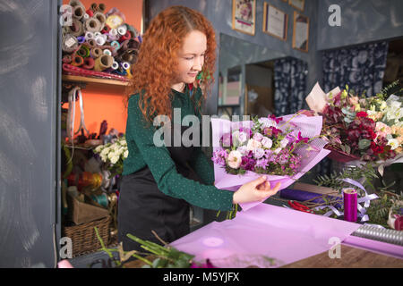 woman selecting colour of paper for flowers at flower shop - Stock Photo