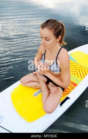 View from top of a  woman practicing  yoga pose on sup board on water - Stock Photo