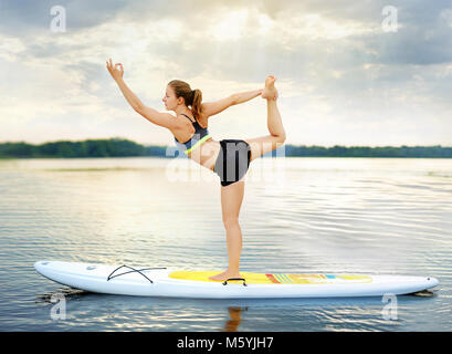Woman practicing Lord of the Dance  yoga Pose balancing on paddle board - Stock Photo