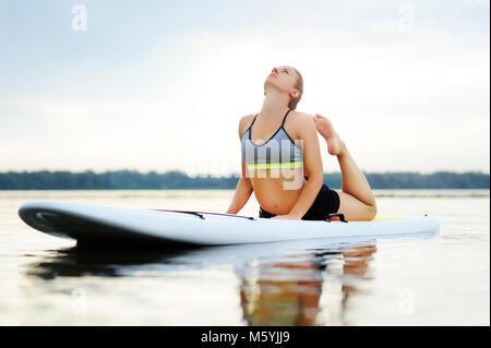 Woman on paddle board practicing snake yoga pose - Stock Photo