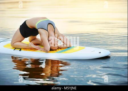Woman practicing Kapotasana yoga Pose on paddle board - Stock Photo