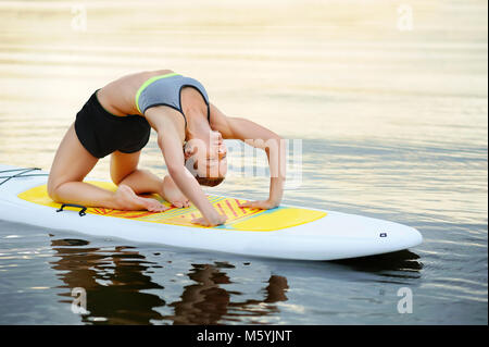 Woman practicing  yoga Pose on a paddle board - Stock Photo