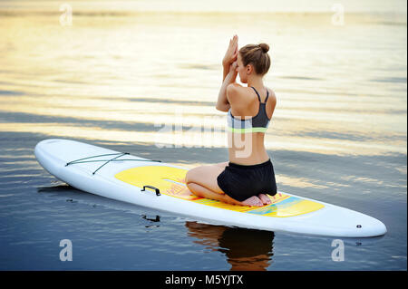 fit woman sitting on exercise ball at the beach smiling at