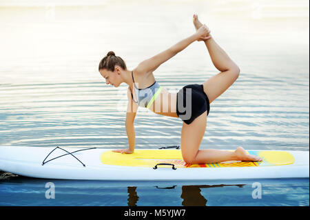 Woman practicing yoga  on paddle board - Stock Photo