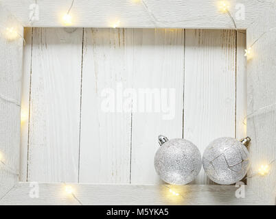 Christmas bright garlands on a wooden light background - Stock Photo