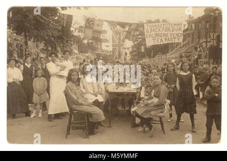 WW1 era postcard of a group of  children sitting down at tables outside in the street for a Peace Party to celebrate - Stock Photo
