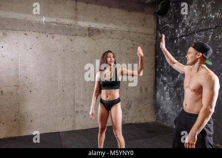 Female trainer giving high five with muscular man - Stock Photo