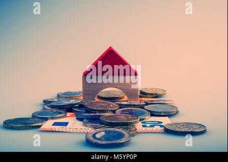 pile of euro coins and paper bills and a house layout on a light background. Business and finance. Business metaphor. - Stock Photo