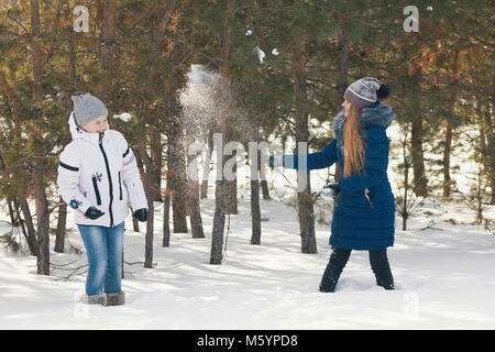Two teenage girls in warm clothes playing snowballs between the trees in the winter - Stock Photo