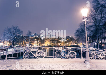 Bicycles under snow on the bridge over Amstel river in Amsterdam in the evening - Stock Photo