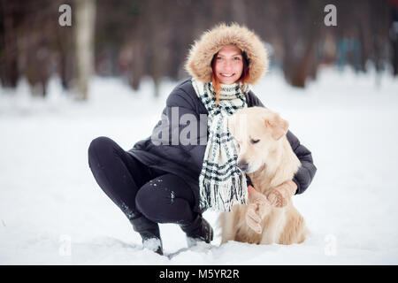 Image of girl in black jacket squatting next to dog in winter - Stock Photo