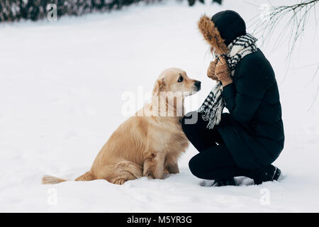 Photo of girl with labrador on walk in winter park - Stock Photo