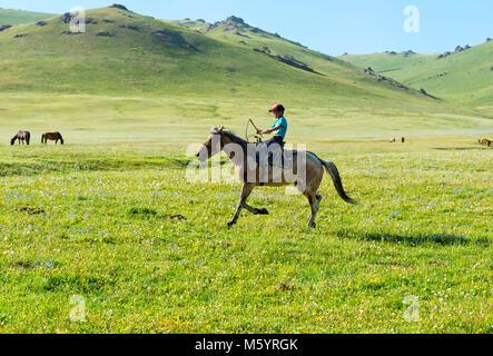 Kyrgyz boy riding his horse, Song Kol Lake, Naryn province, Kyrgyzstan, Central Asia - Stock Photo