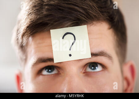 Close-up Of A Businessperson's Forehead With Question Mark On Sticky Note - Stock Photo