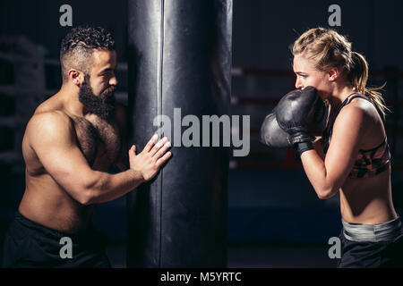 woman working out with boxing gloves and punching bag with her trainer. - Stock Photo