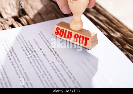 Close-up Of A Red Sold Out Stamp On Document Over Desk - Stock Photo