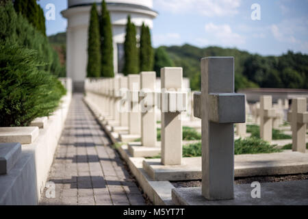 Crosses in cemetery. White gravestones going in perspective - Stock Photo