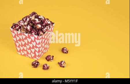 Pink popcorn with berry taste in paper cup on yellow background. - Stock Photo