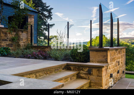 Corner of beautiful, landscaped, private garden (contemporary design, paved path, steps, glass screen, border shrubs, - Stock Photo