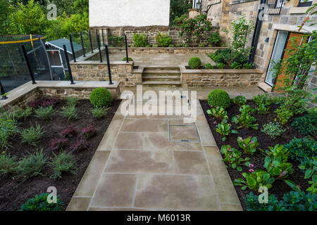 Small corner of beautiful, landscaped, private garden with contemporary design, paved path & steps, border shrubs - Stock Photo