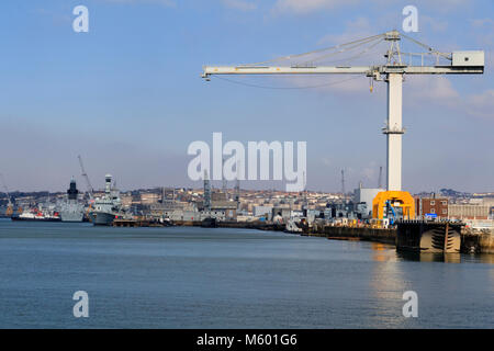 Giant crane dominates the skyline of Devonport Royal Dockyard, Plymouth, Devon.  HMS Somerset and HMS Dragon moored alongside. Stock Photo