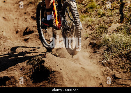 rear wheel sport bike rides on earth dust - Stock Photo