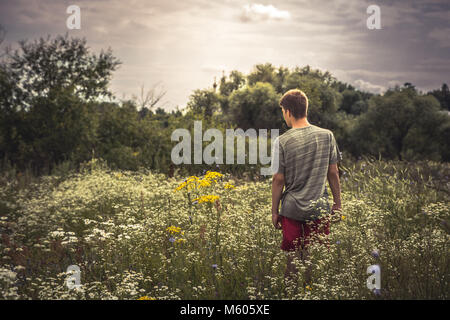 Teenager boy lonely walking summer meadow dramatic moody scenery - Stock Photo