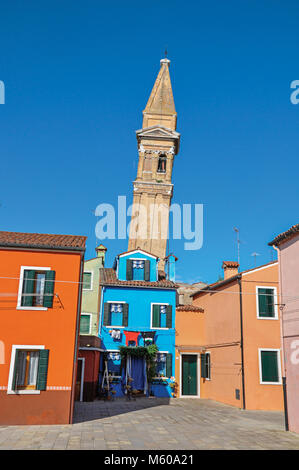 Burano, Italy. Overview of colorful buildings and leaning bell tower in a blue sunny day at Burano, a gracious little - Stock Photo