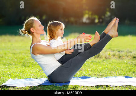Beautiful woman practicing sitting boat yoga pose with her little daughter outdoor - Stock Photo
