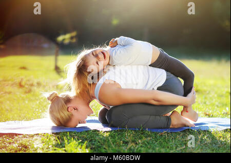 Happy little girl playing with her mom practicing child yoga pose - Stock Photo
