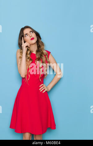 Beautiful young woman in red mini dress is holding hand on chin, looking up and thinking. Three quarter length studio - Stock Photo